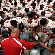 Juarez-Lincoln football coach Aaron Garcia leads the team in prayer before the teams' first ever game against Hidalgo.<br /> Nathan Lambrecht/The Monitor