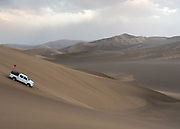 An expedition 4 x 4 car going down a huge dune.