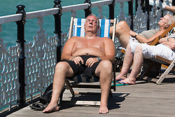 © Licensed to London News Pictures. 06/07/2016. Brighton, UK. Members of the public the advantage of the sunny and warm weather to spend the afternoon sunbathing on the beach in Brighton. Photo credit: Hugo Michiels/LNP
