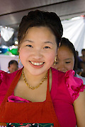 Happy attractive Hmong woman working in a food concession booth. Hmong Sports Festival McMurray Field St Paul Minnesota USA