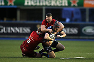 Rhun Williams of Cardiff Blues is tackled by John Ryan (l) and Sammy Arnold of Munster rugby.  Guinness Pro14 rugby match, Cardiff Blues v Munster Rugby at the Cardiff Arms Park in Cardiff, South Wales on Saturday 17th February 2018.<br /> pic by Andrew Orchard, Andrew Orchard sports photography.