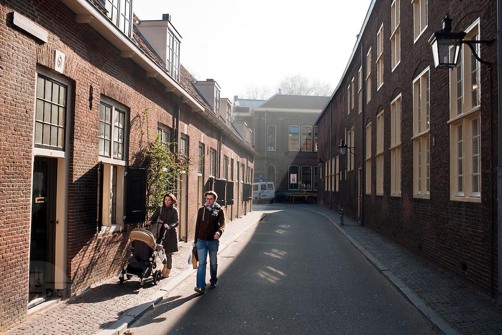 Een man en vrouw lopen met de kinderwagen door een zonnige Nicolaasdwarsstraat in Utrecht.<br /> <br /> A man and woman are walking with a buggy in a sonny Utrecht