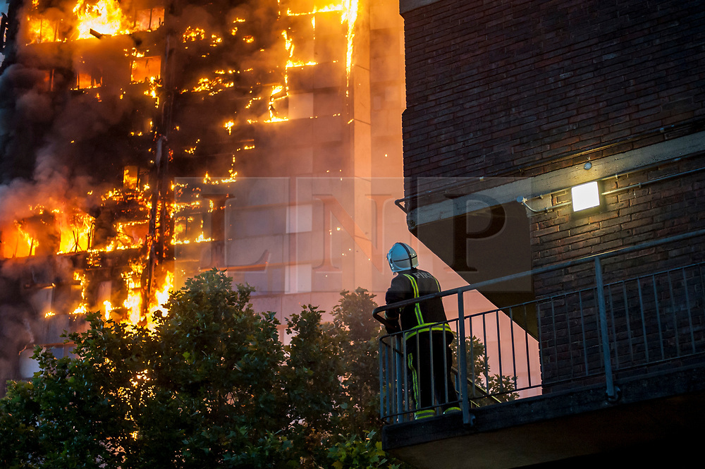 © Licensed to London News Pictures. 14/06/2017. London, UK. A Firefighter looks on at the scene of a huge fire at Grenfell tower block in White City, London. The blaze engulfed the 27-storey building with 200 firefighters attending the scene. There were reports of people trapped in the building. Photo credit: Guilhem Baker/LNP