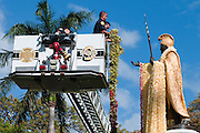 Firemen lifted in a lift to place long lei on the King Kamehameha Statue for King Kamehameha Day in Honolulu, Hawaii.