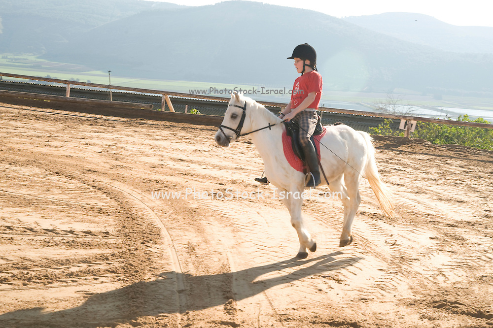 young girl of eight riding a White pony in a corral