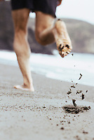 Closeup of sand scattered behind barefoot man running on beach