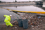 Department of Public Works workers clean up garbage that accumulates in Trash Net boom at the mouth of the Ballona Creek after first rainfall of the year. Urban runoff from heavy rains carries an assortment of styrofoam cups, plastic bottles and bags and other trash that has built up on streets and catch basins since the last rains into the Ballona Creek, a nine-mile waterway that drains the Los Angeles basin. While the boom catches some of this trash, smaller particles and many other pollutants still empty into the Santa Monica Bay and Pacific Ocean. Culver City, Los Angeles, California, USA