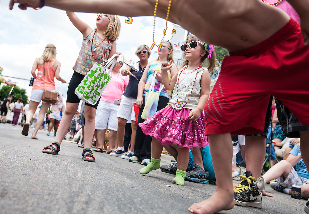 Journei Karth, 3, right (wearing sunglasses) watches the 2015 Ashley Rukes GLBT Pride Parade in Minneapolis June 28, 2015.