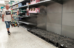 © Licensed to London News Pictures. 21/09/2021. London, UK. A shopper walks past empty shelves of sparkling bottled water in Morrisons, north London, Fears of food shortages grow after two of the UK's biggest Carbon Dioxide (CO2) producers halted production last week due to soaring gas prices. UK food producers and supermarkets are warning that shoppers are likely to face food shortage caused by a lack of gas could hit this week. Photo credit: Dinendra Haria/LNP