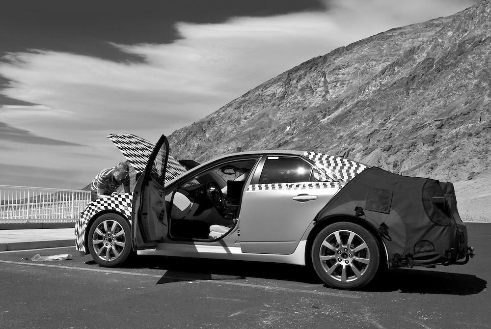 USA, Kalifornien, Death Valley; Ein Mann schaut in den Motorraum eines Autos mit offener Kühlerhaube, das auf einem Parkplatz im Death Valley steht.Der Wagen ist mit einem schachbrettartigen Muster überzogen.Das Death Valley ist einer der heißesten Orte der Erde. |USA, California, Death Valley; A man looks into the engine compartment of a car with an open hood standing on a parking lot in Death Valley. The car is covered with a checkered pattern. Death Valley is one of the hottest places on earth.