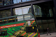 A stripes theme of a London bus promoting the Philippines as a travel destination and reflective designs on the outside a Threadneedle Street building in the City of London. A Londoner walks along the street, passing the bus that's stopped at lights. The scene is at a slant and we see the Filipino countryside of rice terraces with striped rugs, products of that Asian country wanting to attract more foreign tourism from Europe.