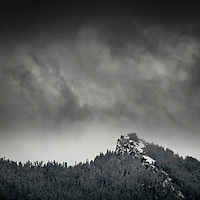a storm arriving with swirling clouds and the season's first snow on the Sawtooth Ridge in the Gifford Pinchot National Forest, Cascade Mountain Range, Washington, USA