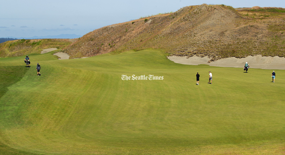 Golfers make their way along the 10th fairway at Chambers Bay public golf course in University Place. (Mike Siegel / The Seattle Times)
