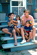 Siblings blowing bubbles with baby sitter ages 18 and 4 thru 7.  St Paul Minnesota USA