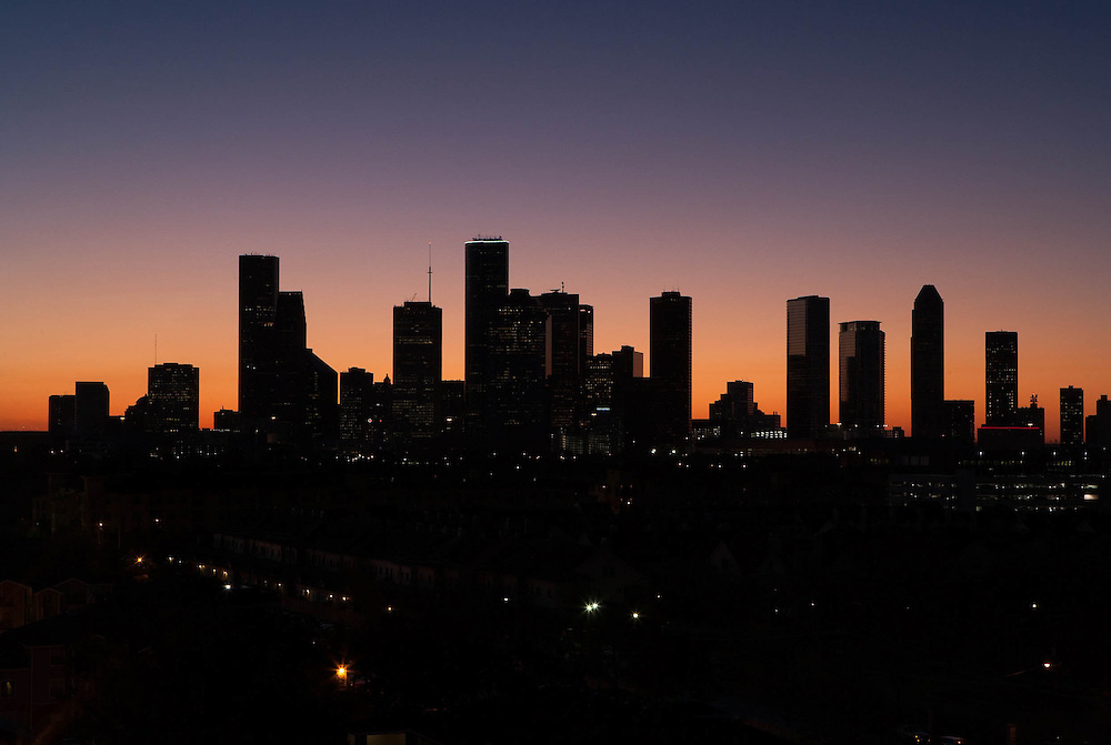 Houston, Texas silhouetted skyline from west with colorful sunset sky.