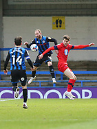 Matt Done of Rochdale  (16) jumps to head the ball under the challenge from a Wigan player during the EFL Sky Bet League 1 match between Rochdale and Wigan Athletic at the Crown Oil Arena, Rochdale, England on 16 January 2021.