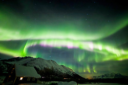 © Licensed to London News Pictures Ltd.  Breivikeidet, Norway. Aurora dramatically lights up the sky over the town of Breivikeidet, Norway, in temperatures of -25 degrees Celsius. Caused by a coronal hole on the sun releasing solar winds a few nights ago which hit our magnetic field on 1st Feb 2019. Photo Credit: Clare Forster/LNP