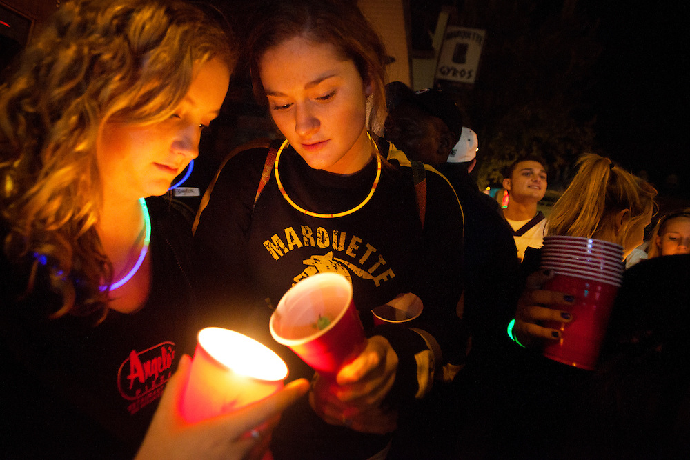 From Left: Bess Featherstone helps light Brittany Byrne's candle.Featherstone and Byrne helped created and organize the even on Facebook.
