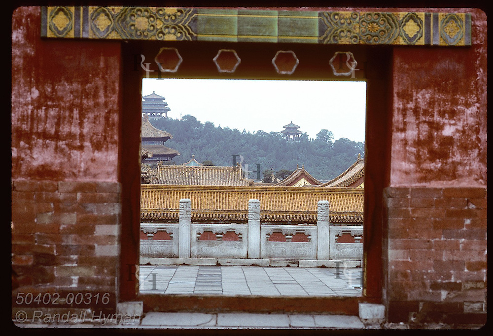 Doorway of a terrace wall inside the Forbidden City frames two pagodas on distant hill; Beijing China