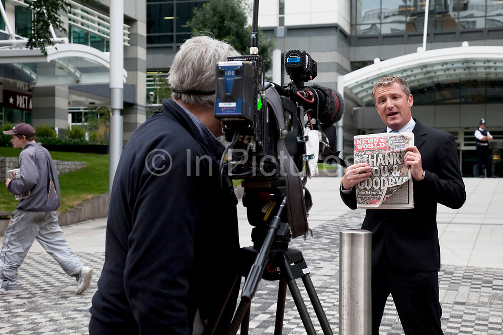 "The last ever copy of tabliod newspaper News of The World is shown to the camera by a news anchor outside their offices in Wapping. Sunday 10th July 2011 saw the end for this most famous of newspapers. Embroiled in the phone hacking scandal, this News International paper had approximately 7 million readers at the time of it's demise. On the cover of this, the final edition, with examples of previous journalistic success the headline simply read ""Thank You & Goodbye""."