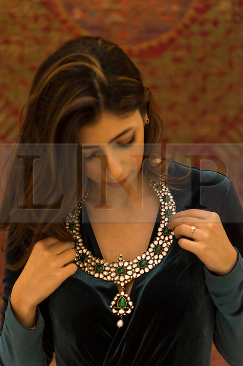 """© Licensed to London News Pictures. 23/10/2020. LONDON, UK. A staff member presents """"An Emerald And Diamond-Set Polychrome Enamelled Necklace (Khanti)"""", North India, Late 19th Century, (Estimate GBP40,000-60,000), at Sotheby's, New Bond Street during the preview of their auction of Treasures from the Islamic World on October 27.  Photo credit: Stephen Chung/LNP"""