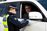 Police are seen checking drivers licences at a roadblock south of Gisborne as Melbourne plunges back into Stage 3 lockdowns during COVID-19. After a sustained outbreak across Melbourne, Stage 3 lockdowns re-commence across the city today along with one regional shire, Mitchell. Residents can only leave their home for four reasons from midnight last night. Police are setting up roadblocks across Melbourne to stop anyone flouting the rules and will check an unprecedented number of drivers as well as door knock the effected areas. Stats across Australia are now completely closing their borders to Victorians. This comes after 118 new coronavirus cases being discovered Tuesday night bringing the total cases in Victoria to 860. (Photo be Dave Hewison/ Speed Media)