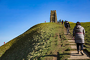 Families use the concrete paths, climbing to Glastonbury Tor, the ruins of St Michaels tower that sits on top of the hill in Glastonbury, Somerset. <br /> A prominent hill overlooking the Isle of Avalon, Glastonbury and the Somerset Levels. It has been a site of religious significance for over 1000 years and is considered one of the most spiritual sites in the United Kingdom, especially for Pagans.