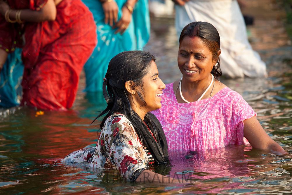 Indian Hindu pilgrims bathing in The Ganges River at Dashashwamedh Ghat in Holy City of Varanasi, Benares, India