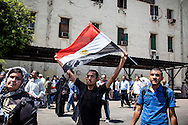 Muslim Brotherhood supporters watch a military helicopter fly overhead.