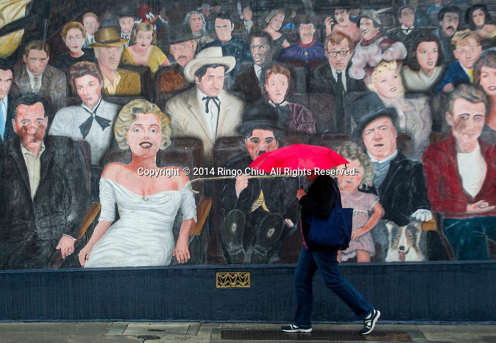 12月2日,美國加利福尼亞州洛杉磯,一名行人舉傘經過在好萊塢大道附近的一幅明星牆畫。當天南加州迎來秋天第一場暴雨,將為今年面臨嚴重乾旱問題的加州帶來2至5寸雨水。 同時,當局亦發出警告,洪水、土石流可能會襲擊部分地區。 (新華社發 趙漢榮攝)<br /> A pedestrian carries an umbrella as she walks by a mural in Hollywood, California, Tuesday, December 2, 2014. California is bracing for the arrival of a new, more powerful Pacific storm following a weekend of scattered rain, showers and snow. The National Weather Service says a low-pressure system off the coast will draw a plume of subtropical moisture northward into the state beginning on Tuesday.  (Xinhua/Zhao Hanrong)(Photo by Ringo Chiu/PHOTOFORMULA.com)