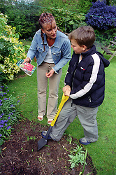 Single mother gardening with young son,