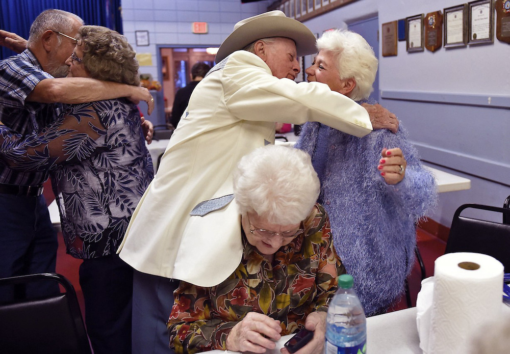 Reaching over his wife, Arnold embraces Jeraldine Shouse before the start of a dance at the Frankfort Veterans of Foreign Wars.