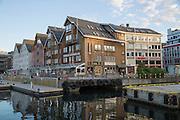 Historic wooden buildings bars and restaurants along harbour waterside,  Tromso, Norway