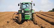 Farm machinery preparing and planting a crop of potatoes in a field, Shottisham, Suffolk, England
