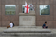 While a shrine of flowers and messages continue to grow ten days after the terrorist attack on London Bridge and Borough Market, the Griffin marking the southern-most boundary of the City of London - the capital's financial district - has been draped with the English flag (aka the Cross of St. George), on 12th June 2017 in London, England. Near the southern-most boundary of the City of London, where tLondoners and visitors to the capital leave their emotional and defiant poems and personal messages on post-it notes.