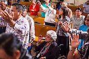 "12 JULY 2012 - FT DEFIANCE, AZ:  Sister ANGIE BOWMAN (center) joins the crowd at the alter call of the 23rd annual Navajo Nation Camp Meeting in Ft. Defiance, north of Window Rock, AZ, on the Navajo reservation. Preachers from across the Navajo Nation, and the western US, come to Navajo Nation Camp Meeting to preach an evangelical form of Christianity. Evangelical Christians make up a growing part of the reservation - there are now more than a hundred camp meetings and tent revivals on the reservation every year. The camp meeting in Ft. Defiance draws nearly 200 people each night of its six day run. Many of the attendees convert to evangelical Christianity from traditional Navajo beliefs, Catholicism or Mormonism. ""Camp meetings"" are a form of Protestant Christian religious services originating in Britain and once common in rural parts of the United States. People would travel a great distance to a particular site to camp out, listen to itinerant preachers, and pray. This suited the rural life, before cars and highways were common, because rural areas often lacked traditional churches.PHOTO BY JACK KURTZ"