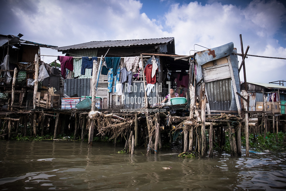 A woman doing her washing in her house on stilts in the Mekong Delta, Vietnam