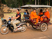 "14 MARCH 2105 - SIEM REAP, SIEM REAP, CAMBODIA: Buddhist monks use a tuk-tuk (three wheeled taxi) in Angkor Thom, a part of the Angkor Wat complex. The area known as ""Angkor Wat"" is a sprawling collection of archeological ruins and temples. The area was developed by ancient Khmer (Cambodian) Kings starting as early as 1150 CE and renovated and expanded around 1180CE by Jayavarman VII. Angkor Wat is now considered the seventh wonder of the world and is Cambodia's most important tourist attraction.   PHOTO BY JACK KURTZ"