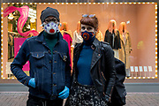 As the Coronavirus pandemic spreads across the UK, businesses and entertainment venues not already closed with the threat of job losses, struggle to stay open with growing rumours of a lockdown and travel restrictions around the capital. As the majority of Londoners start to work from home, others like Simon and Emily wear face masks in front of a shop on Carnaby Street, on 19th March 2020, in London, England.