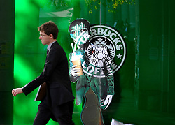 © Licensed to London News Pictures. 02/11/2011. London, UK. A man in a suit walks past a Starbuck logo with a figure added. Occupy London protesters outside St Paul's Cathedral today, 2nd November 2011.  Photo credit : Stephen Simpson/LNP