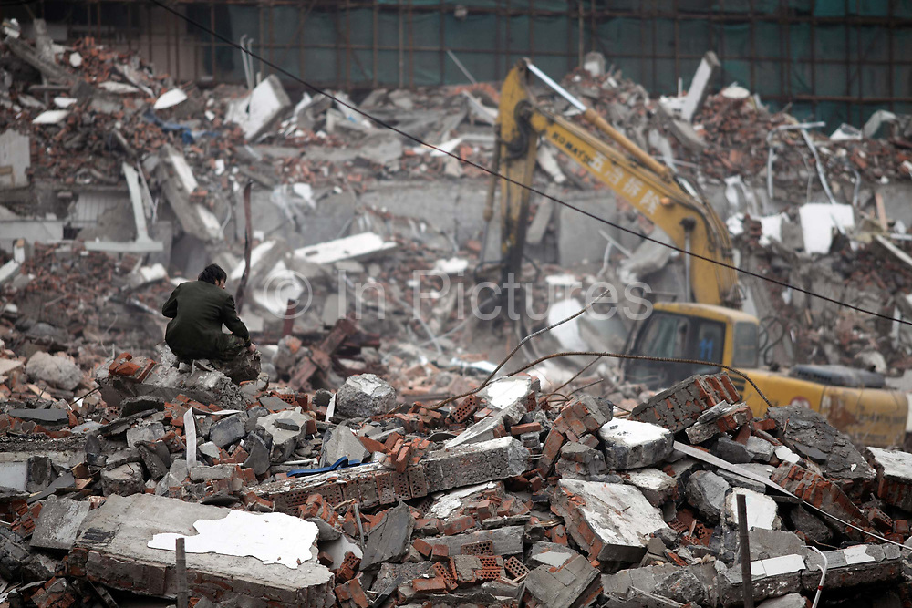 A man squats on top of a pile of rubble at a demolition site for real estate redevelopment in Shanghai, China on 10 December, 2009.   Despite repeated efforts by government to rein in housing prices, housing in major cities in Shanghai and Beijing have changed little from their peaks  and the flow of hot money into smaller cities have fueled additional bubbles.