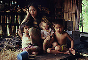 Twenty three years ago: Seventeen year old Den Along (LHS) daughter of Along Sega the renowned resistance fighter, with her daughter Senorita, 1yr old (child in the middle). They are indigenous Penan native people, living as semi-nomadic hunter gatherers. Long Tegang, Limbang district, Sarawak, Borneo 1989<br /> <br /> <br /> PENAN SULAP, MALAYSIA. Sarawak, Borneo, South East Asia. Penan family in sulap settlement. Tropical rainforest and one of the world's richest, oldest eco-systems, flora and fauna, under threat from development, logging and deforestation. Home to indigenous Dayak native tribal peoples, farming by slash and burn cultivation, fishing and hunting wild boar. Home to the Penan, traditional nomadic hunter-gatherers, of whom only one thousand survive, eating roots, and hunting wild animals with blowpipes. Animists, Christians, they still practice traditional medicine from herbs and plants. Native people have mounted protests and blockades against logging concessions, many have been arrested and imprisoned.