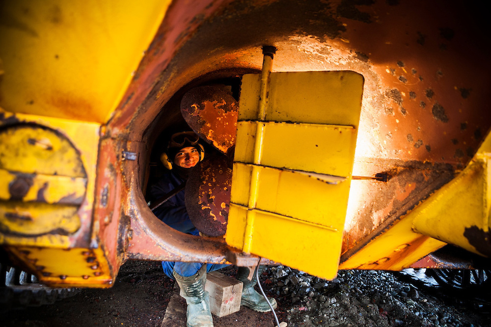 Electrical engineer Jacek Renkas scrubs rust from the hull of a Soviet-era amphibious vehicle still in use at the Polish Polar Station in Hornsund, Svalbard.