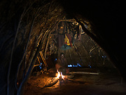 Cooking inside the home of a Hadza, made of branches and grass. At the Hadza camp of Dedauko.