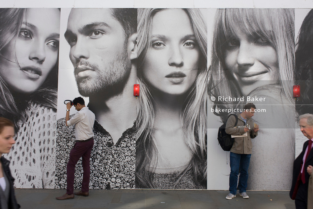 Londoners stand beneath the panels of a large poster for the H&M clothing brand on Regent Street, London.
