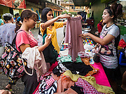 30 DECEMBER 2015 - BANGKOK, THAILAND:   People buy used clothes as a street stall in Bang Chak Market. The market is supposed to close permanently on Dec 31, 2015. The Bang Chak Market serves the community around Sois 91-97 on Sukhumvit Road in the Bangkok suburbs. About half of the market has been torn down. Bangkok city authorities put up notices in late November that the market would be closed by January 1, 2016 and redevelopment would start shortly after that. Market vendors said condominiums are being built on the land.           PHOTO BY JACK KURTZ