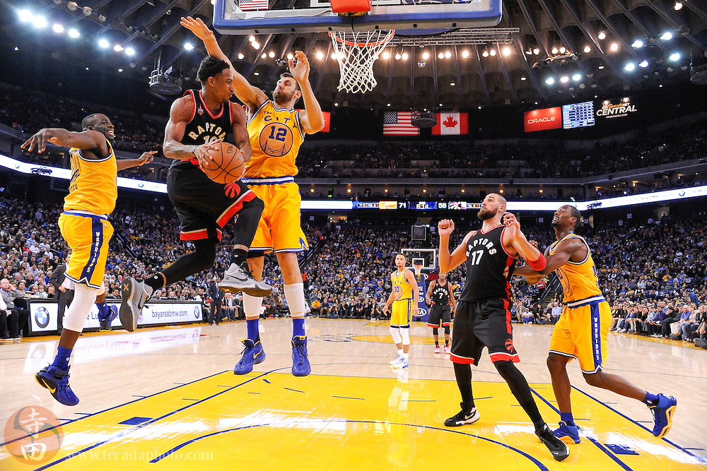 November 17, 2015; Oakland, CA, USA; Toronto Raptors guard DeMar DeRozan (10) passes the basketball against Golden State Warriors center Andrew Bogut (12) during the third quarter at Oracle Arena. The Warriors defeated the Raptors 115-110.