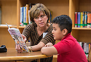 Read Houston Read volunteer Kimberly Thompson guides a student through an exercise at Sutton Elementary School, November 3, 2014.