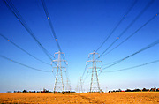 Electricity transmission power lines held by pylons crossing fields in countryside, Suffolk, England, UK
