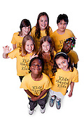 A group of children wearing yellow t-shirts looking up, wavings, smiling and hugging.